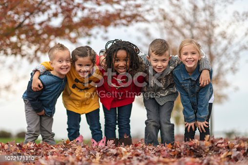 Five friends are standing outside with their arm around each other. They are outside on a fall day. They are smiling at the camera. There are fallen leaves on the ground.