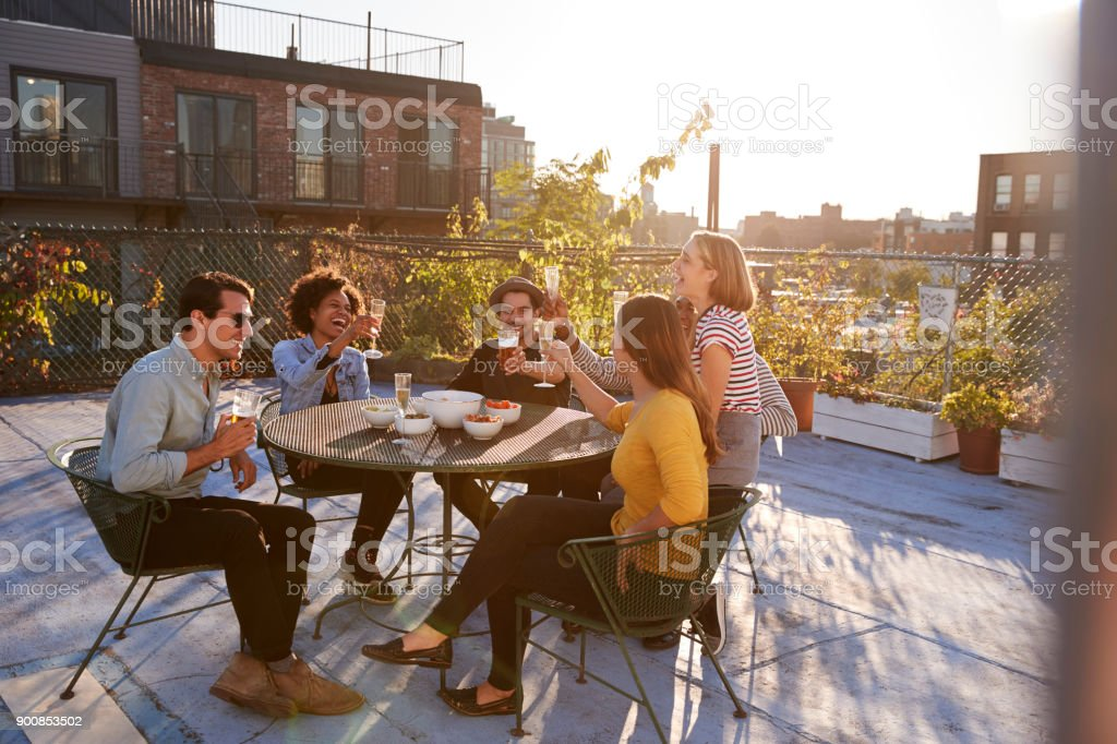 Five friends sitting at a table on a rooftop making a toast - foto stock