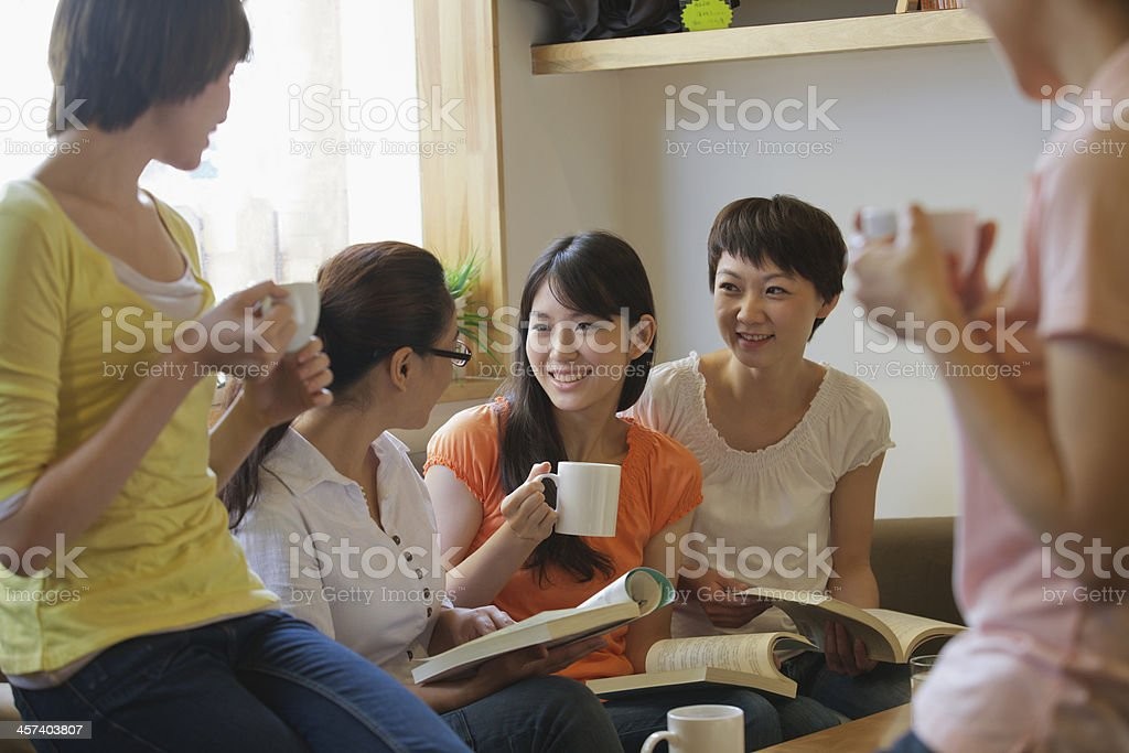 Five friends sitting in coffee shop, reading, discussing stock photo