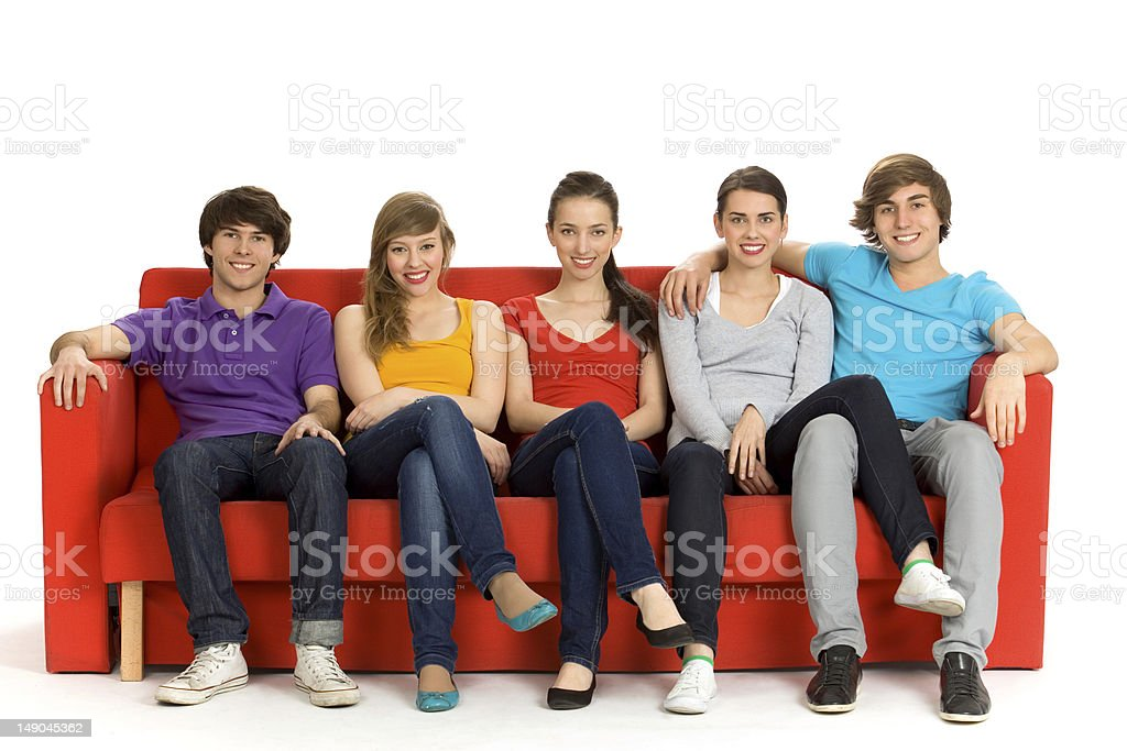 Five friends sitting on a red couch royalty-free stock photo