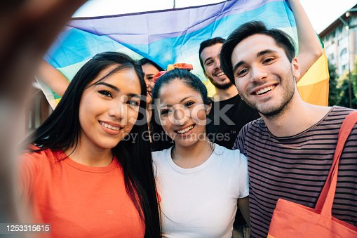 Five friends taking a selfie together at an LGBTQI Pride event. Hispanic and caucasian ethnicities. They are looking at camera and smiling.