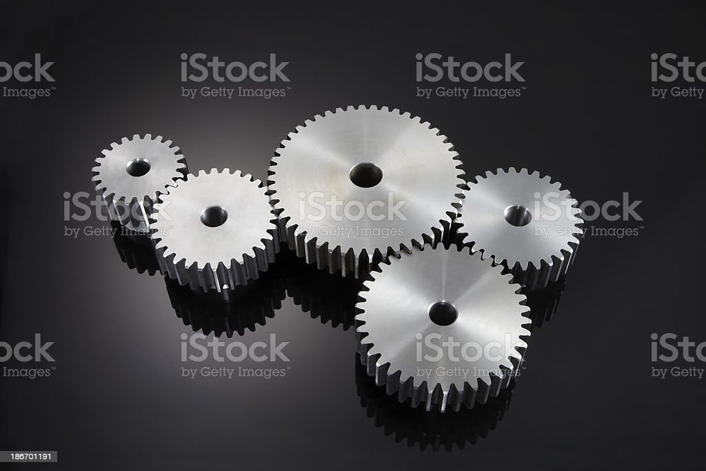 Five gears turning in motion on a black background stock photo