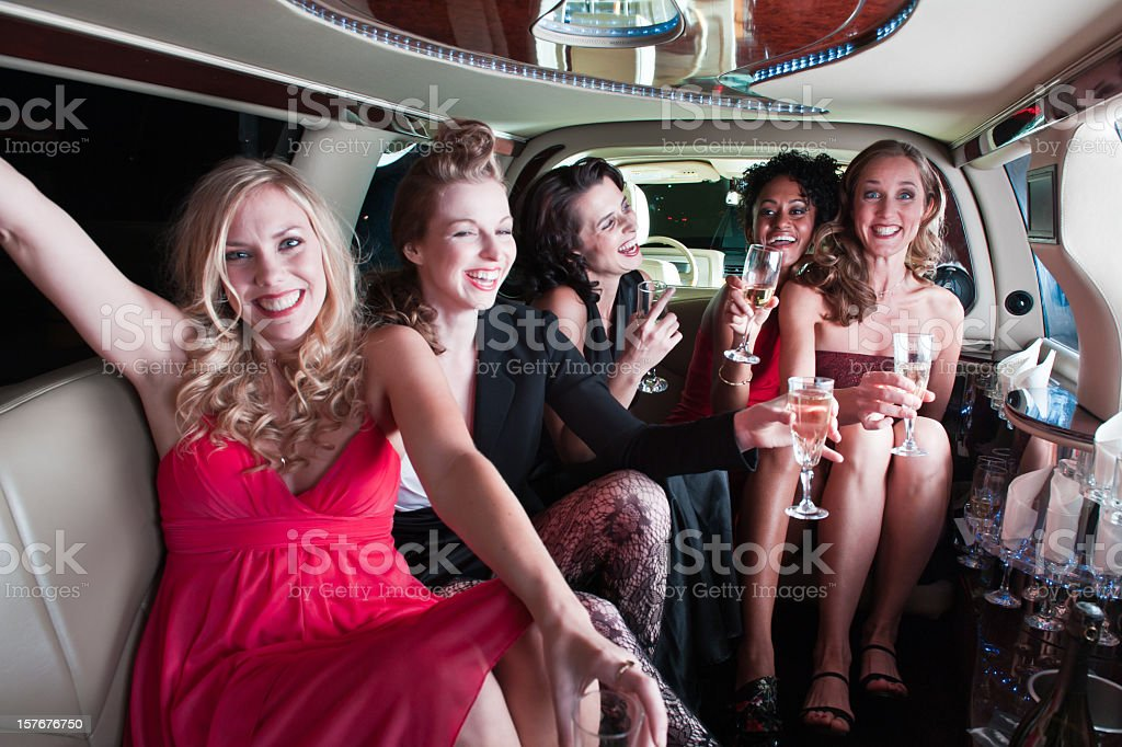 Five girls in a limo drinking and partying stock photo