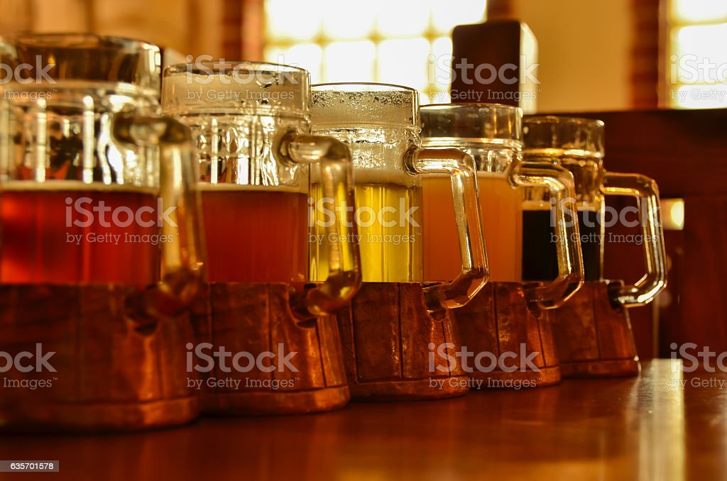 Five  glasses of beer stand in row on bar table royalty-free stock photo