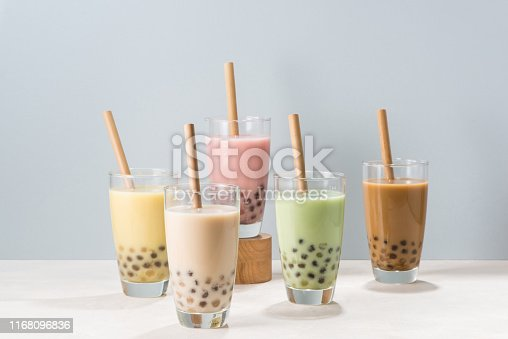 Five glasses of healthy milky boba or bubble tea flavored with fresh fruit and chocolate and served with traditional wide straws