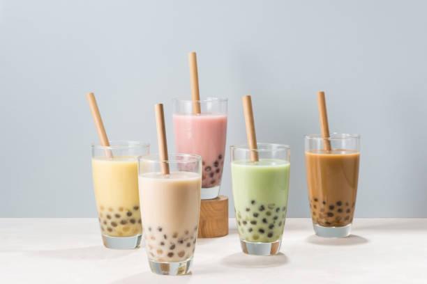 fünf gläser gesunden milchigen boba oder bubble tea mit frischem obst und schokolade gewürzt und mit traditionellen breiten strohhalmen serviert - grape sugar stock-fotos und bilder
