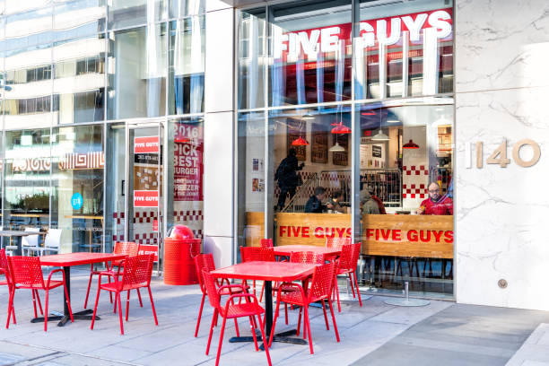 Five Guys restaurant, store burger chain entrance in District of Columbia with chairs, tables, outside, outdoor sitting area, people inside eating stock photo