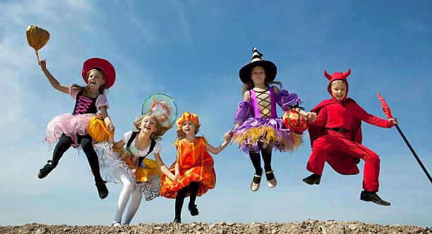 Fünf Halloween-Kinder Springen in den Himmel. – Foto
