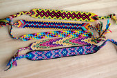 Five handmade homemade colorful natural woven bracelets of friendship on wooden board, group of fashion accessories, various colors