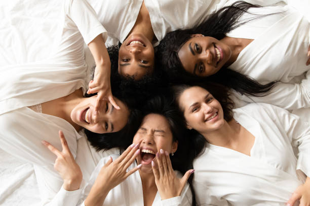 five happy diverse young girls lying on bed, top view - só mulheres imagens e fotografias de stock