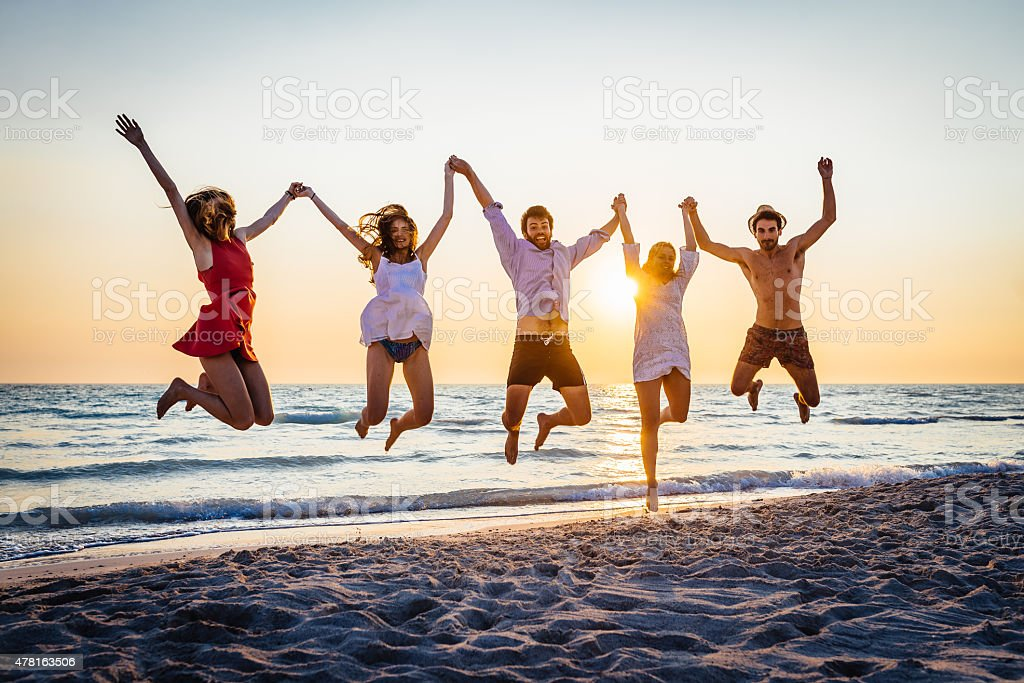 Five happy friends jumping on the beach for summer stock photo
