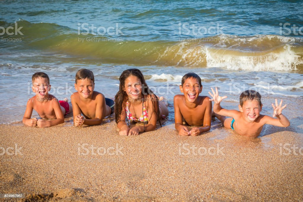 Five happy kids lying down together on the beach stock photo
