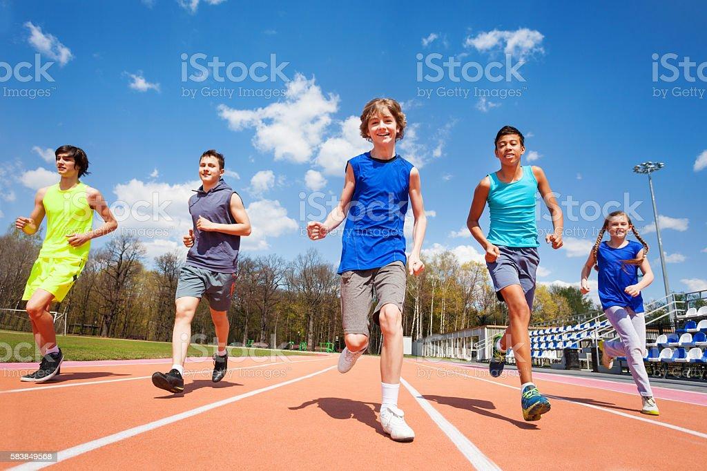 Fünf glückliche Teenager- und -kinder laufen im Stadion - Lizenzfrei Kind Stock-Foto