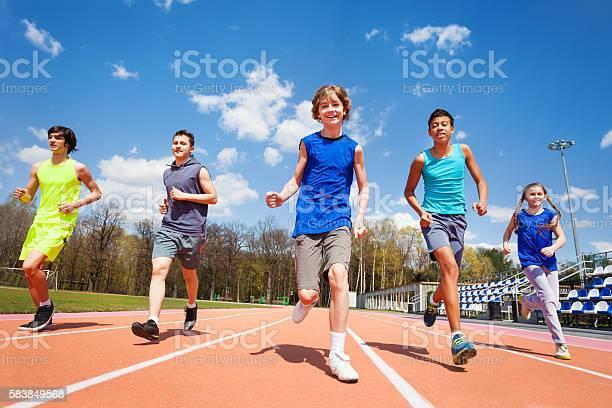 Fünf Glückliche Teenager Und Kinder Laufen Im Stadion Stockfoto und mehr Bilder von Kind