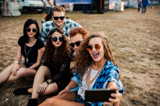 five happy teenagers sitting in the meadow taking selfie - concert selfie stock photos and pictures