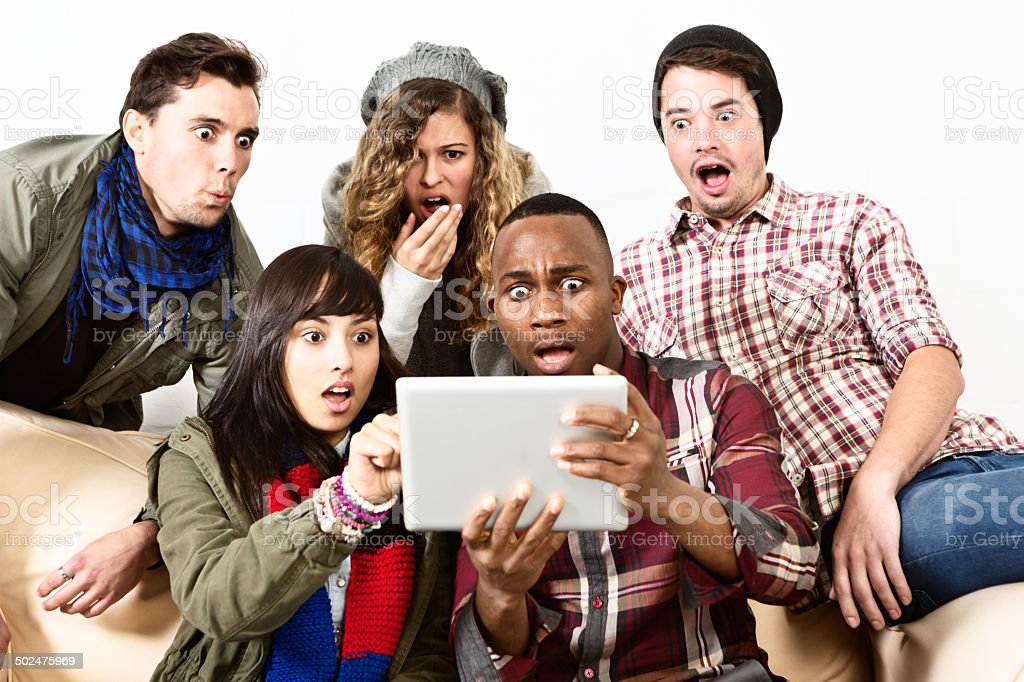 Five horrified young people see shocking image on digital tablet stock photo