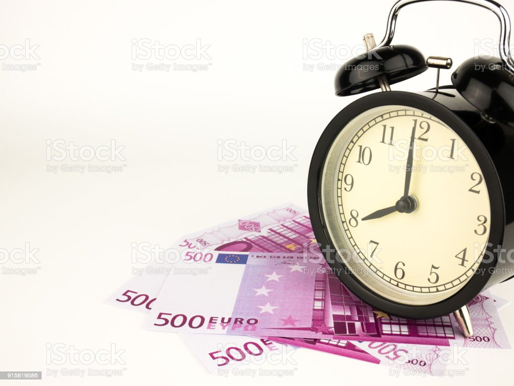 Five hundred 500 Euro bills banknotes with Alarm clock, European currency money background stock photo