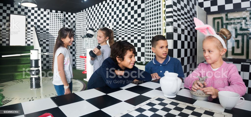 five  kids discuss the game in the chess quest room stock photo