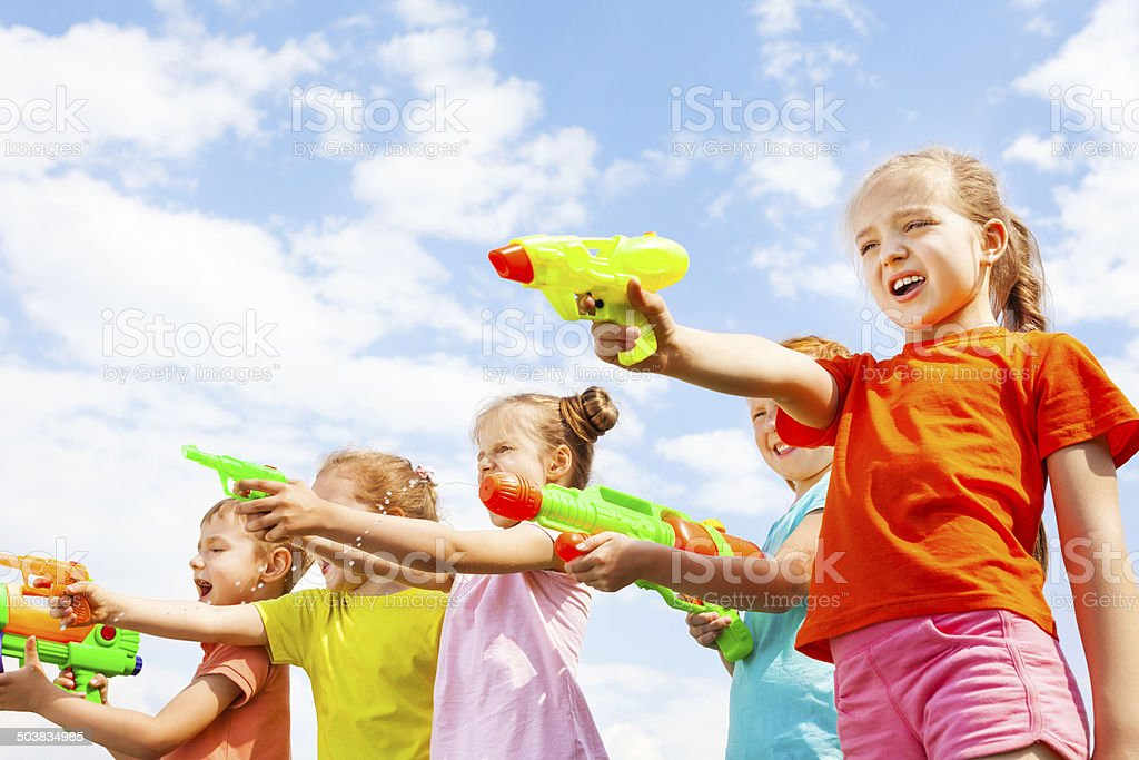 Five kids play with water guns stock photo