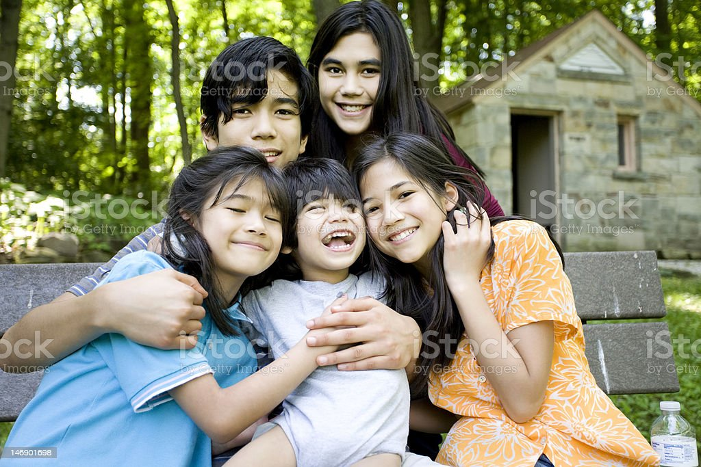 Five kids sitting on bench happy and hugging stock photo
