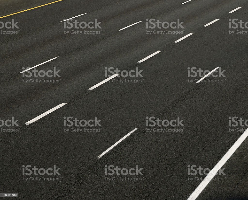 Five lanes of a very wide highway with white dashed lines royalty-free stock photo