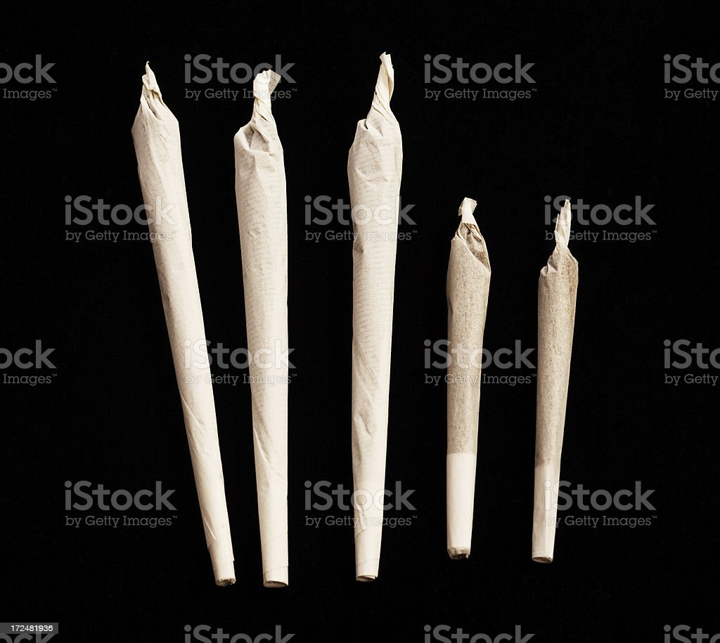 Five marijuana joints, three large and two small on black stock photo
