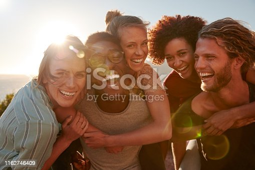 Five millennial friends on a road trip have fun piggybacking at the roadside, front view, lens flare