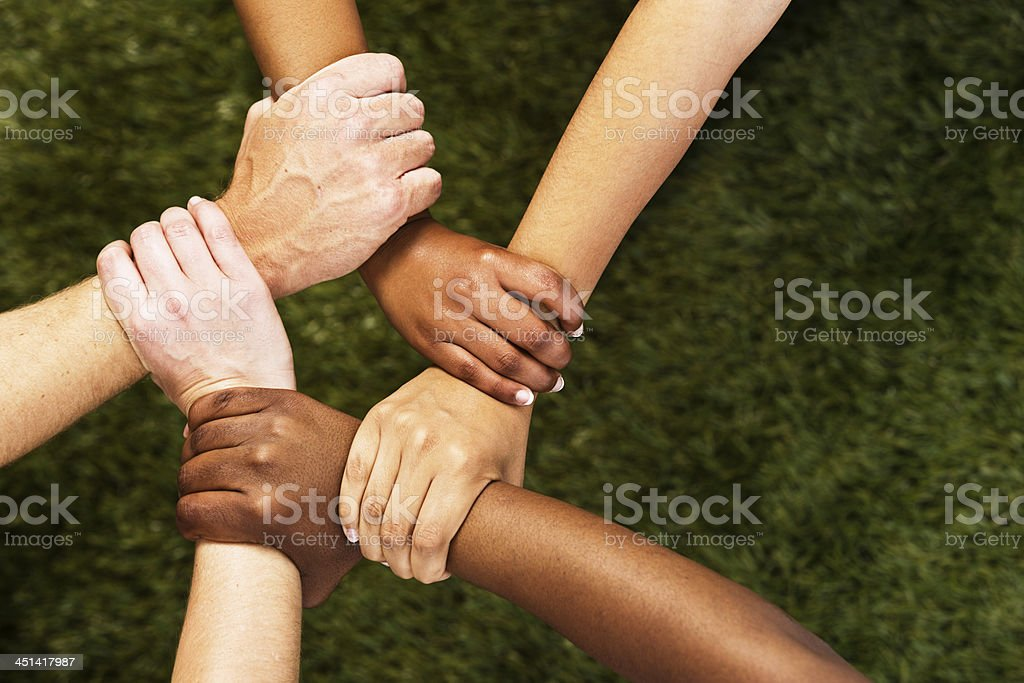 Five mixed hands clasped in unity against grass stock photo