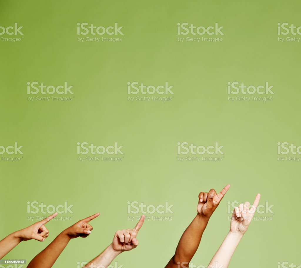 Five mixed hands point upwards and to the side against a green...