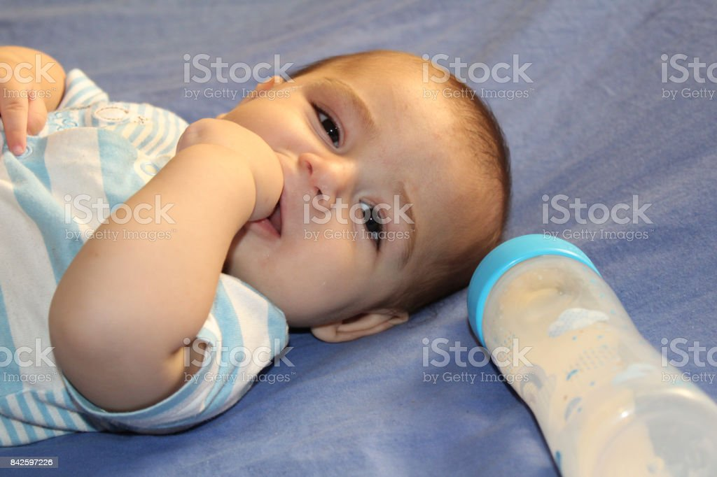 Five months old baby boy playing with bottle on the bed stock photo