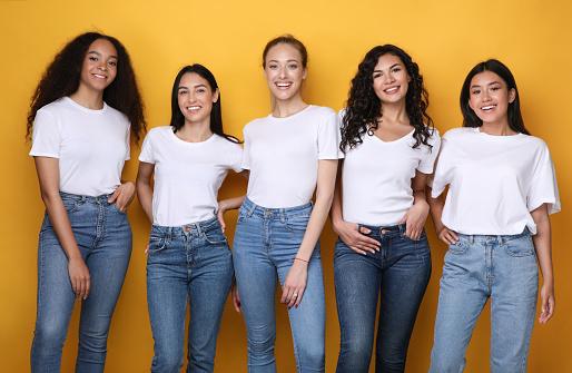 Five Multiethnic Models Girls Smiling Standing In Studio, Yellow Background