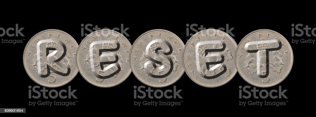 RESET – Five new pence coins on black background stock photo