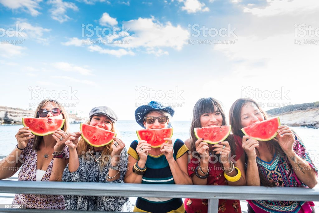 five nice happy young females caucasian eating watermelon to celebrate summer time and warm day with sun near the ocean. beautiful colors for group of friends people together eating fruits and smiling craziness stock photo