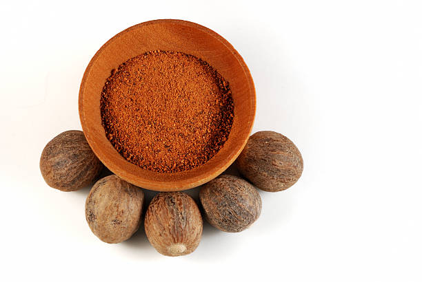 Five Nutmeg nuts and powder stock photo