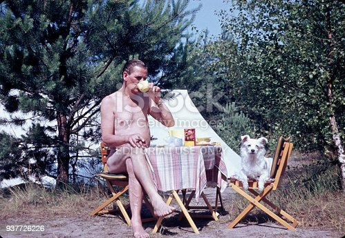 Baltic Sea, Germany, 1960. A camper, in company with his dog, enjoys a cup of coffee in front of his tent.