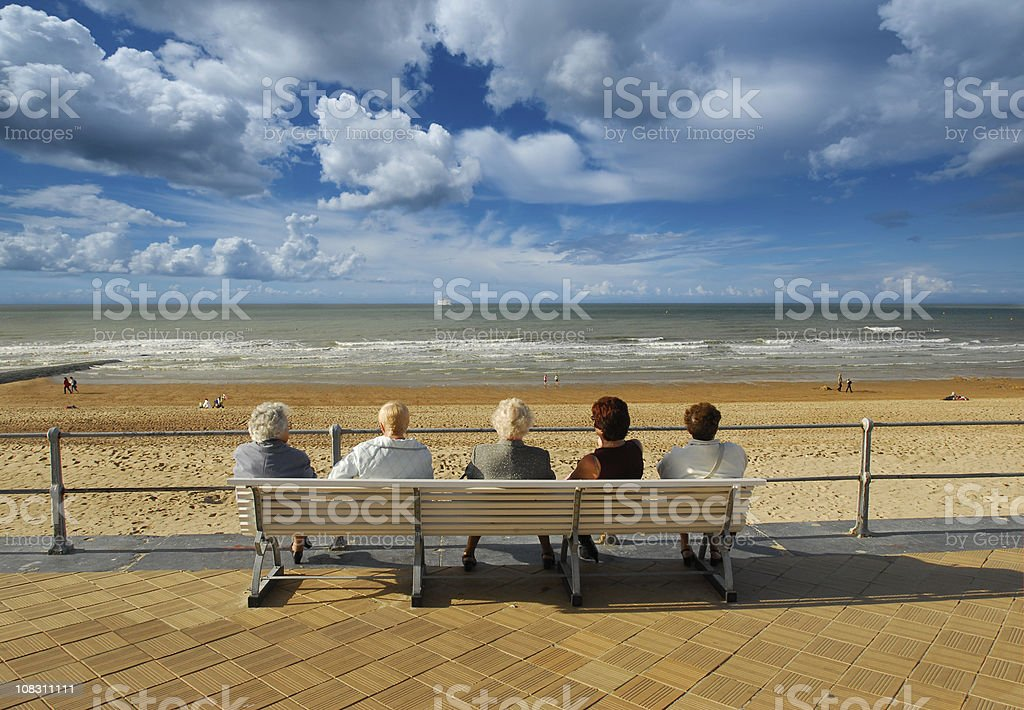 Five Old ladies sitting on bench chilling out near sea royalty-free stock photo