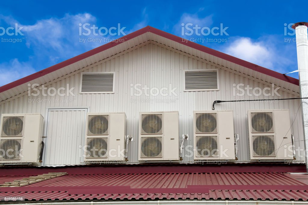 Five outdoor units of air conditioners on the wall stock photo