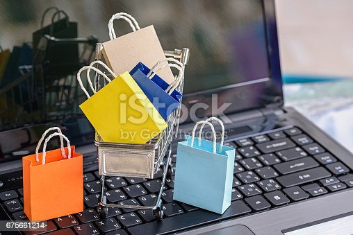 Five paper shopping bags and a shopping cart on a laptop keyboard. Concept about online shopping that customers can buy everything from home or office and the messenger will deliver to the doorstep.