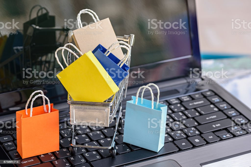 Five paper shopping bags and a shopping cart on a laptop keyboard. stock photo