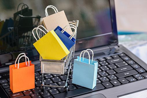 Five Paper Shopping Bags And A Shopping Cart On A Laptop Keyboard - Fotografie stock e altre immagini di Acquisti a domicilio