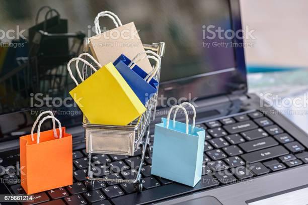Cinque Borse Della Spesa Di Carta E Un Carrello Della Spesa Su Una Tastiera Per Laptop - Fotografie stock e altre immagini di Shopping online