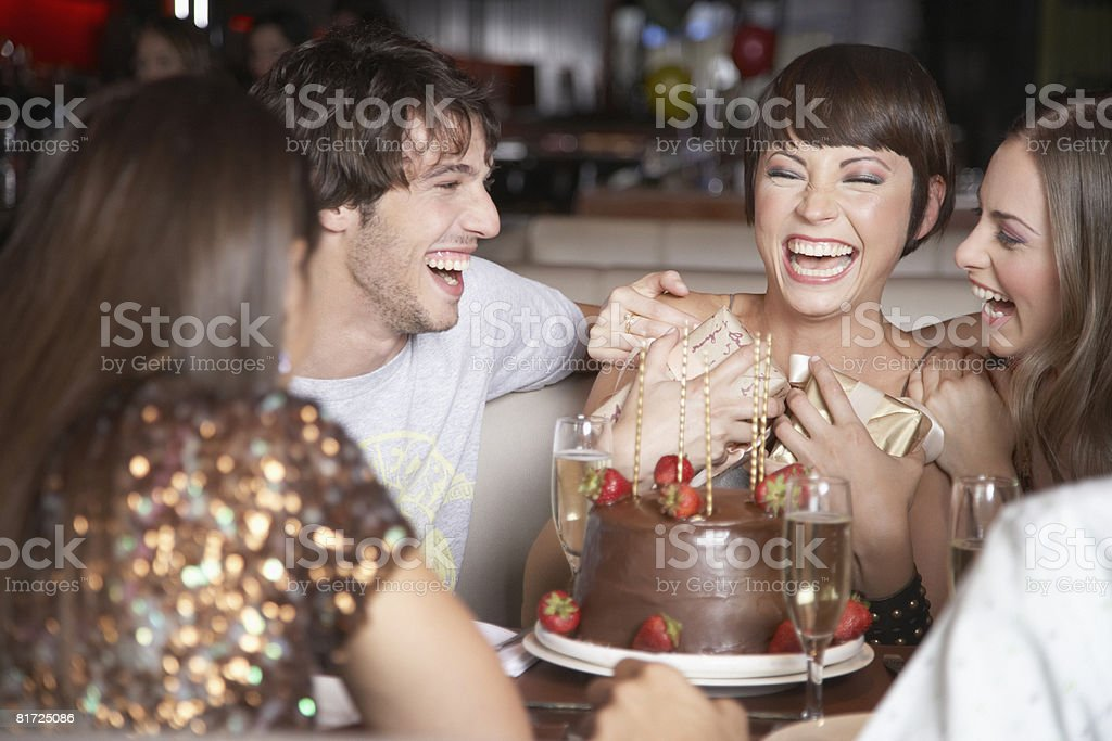 Five people having fun and laughing at a birthday party in a restaurant stock photo