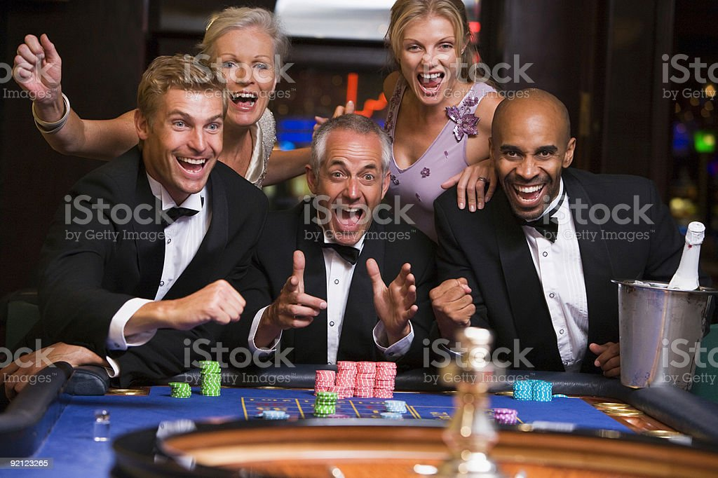Five people in casino playing roulette stock photo