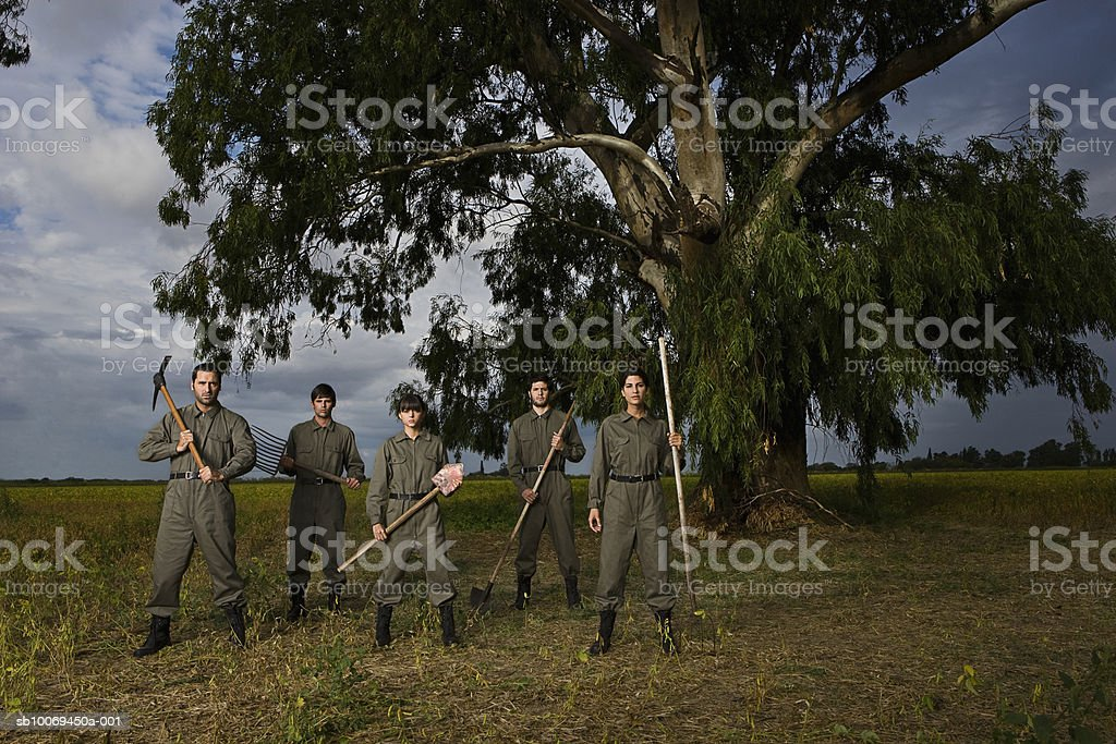 Five people in military uniform standing in field, portrait royalty free stockfoto