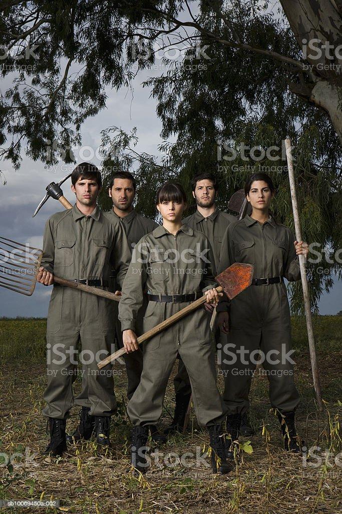 Cinque persone in uniforme militare in piedi in campo, verticale foto stock royalty-free