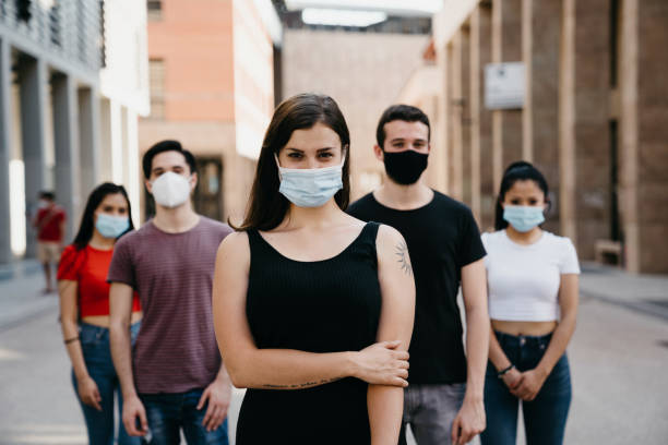 Five people looking at camera, wearing face masks in the city stock photo