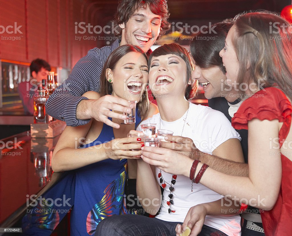 Five people with shots in nightclub toasting and smiling royalty-free stock photo