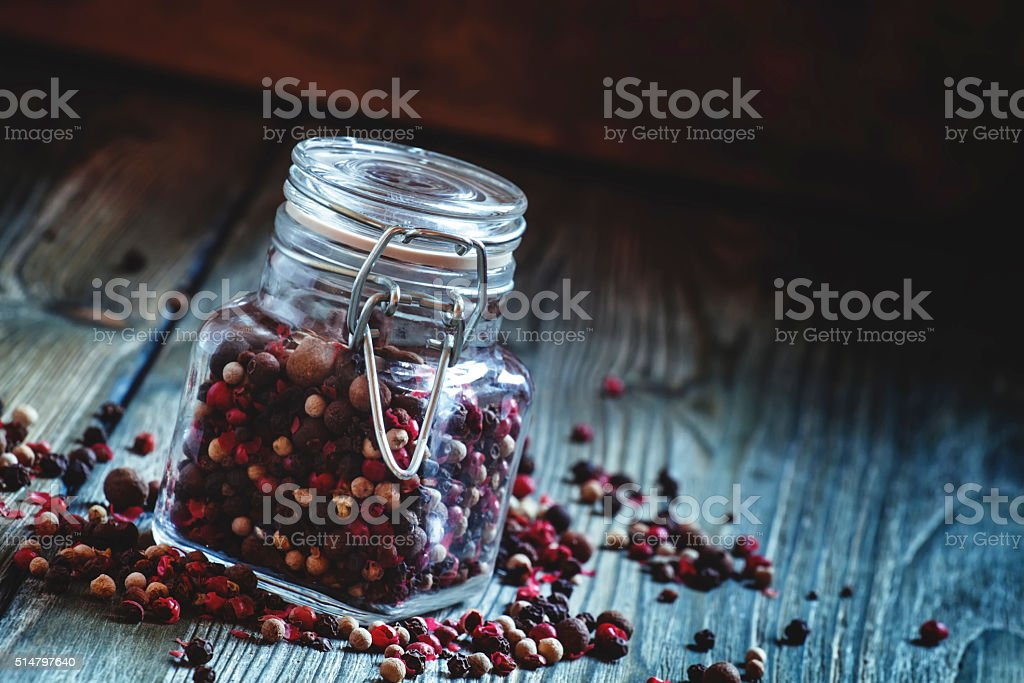 Five peppers in a jar, dark toned image stock photo