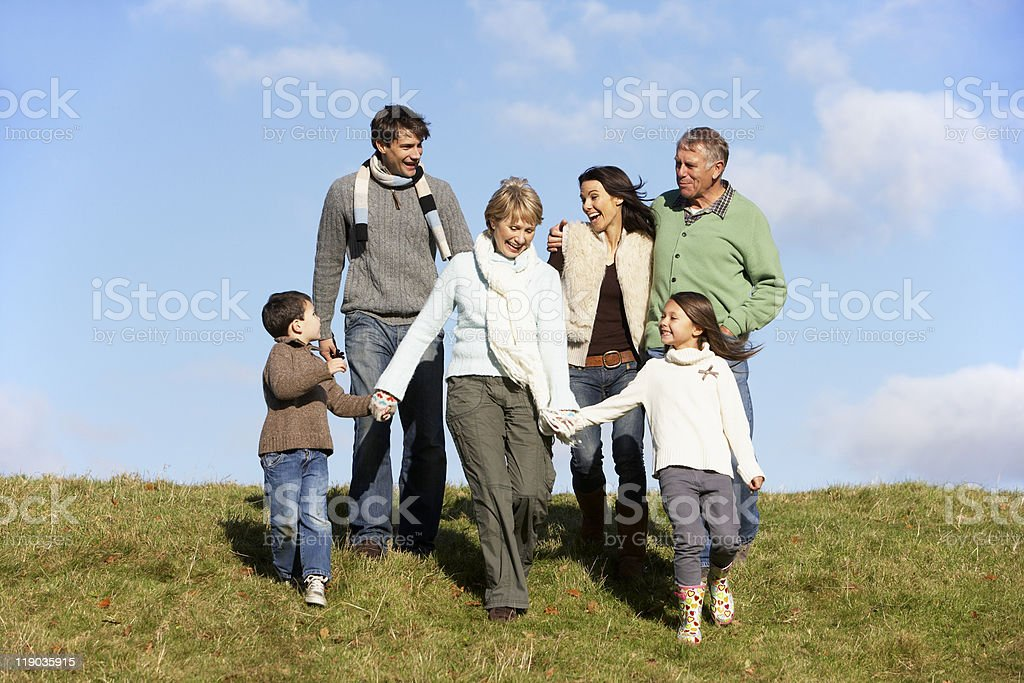 Five person family walking in the park on a sunny day royalty-free stock photo