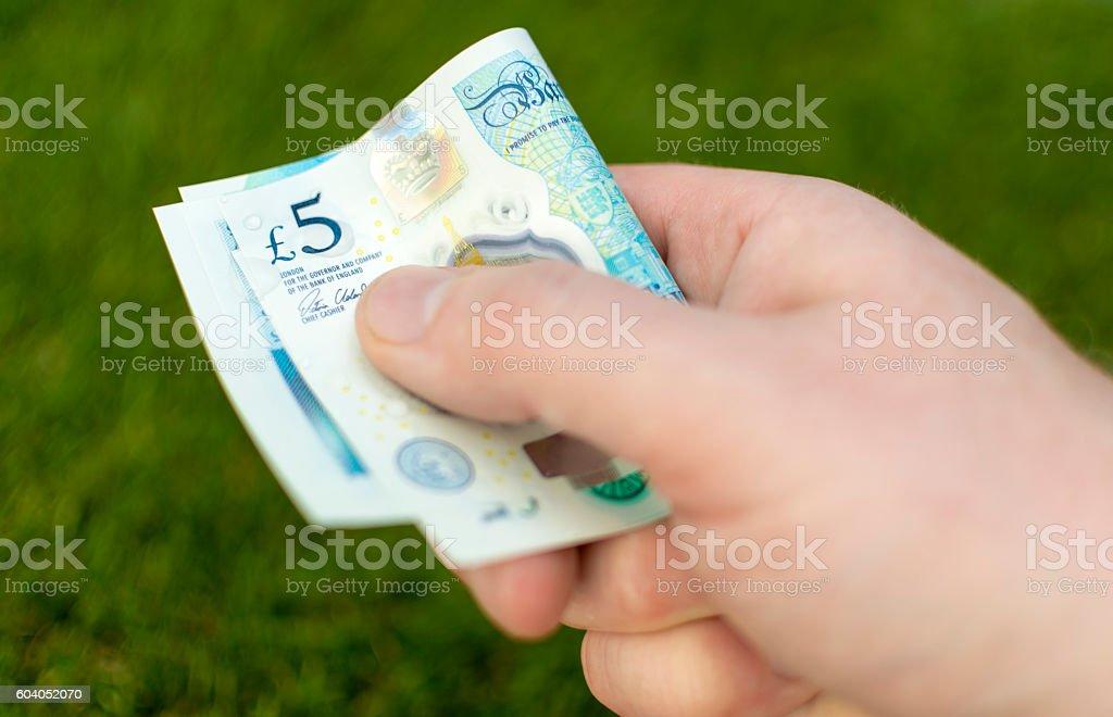 2016 UK Five Pound Note - Folded over grass stock photo